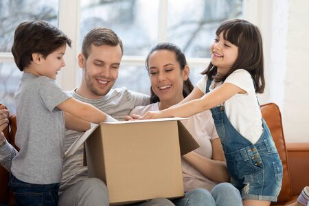 Foto de Happy family with kids customers renters open cardboard box receive parcel unpack after relocation, cute children helping parents unbox package at home, post shipping delivery and moving day concept - Imagen libre de derechos