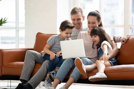 Photo pour Happy family of four parents and cute little kids children enjoy using laptop watching cartoons, make internet video call or shopping online looking at computer screen sit together on sofa at home - image libre de droit