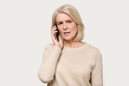 Photo for Serious senior mature woman isolated on grey studio background hold cellphone talking discussing problems, focused aged lady using smartphone, speak with wireless 5g connection, technology concept - Royalty Free Image