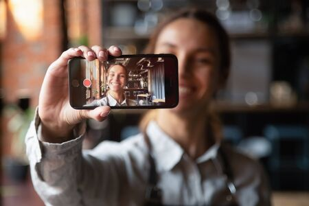 Foto de Happy young waitress vlogger holding smartphone recording video blog on mobile display, smiling millennial cafe owner coffeehouse worker blogger girl wear apron shooting vlog looking at phone camera - Imagen libre de derechos