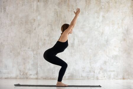 Foto de Beautiful young woman wearing black sportswear practicing yoga, doing Chair exercise, standing in Utkatasana pose side view, sporty girl working out at home or in yoga studio with grey walls - Imagen libre de derechos