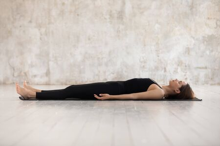 Photo pour Young woman wearing black sportswear practicing yoga, doing Corpse, Savasana exercise, relaxing, lying in Dead Body pose on mat, sporty girl working out at home or in yoga studio with grey walls - image libre de droit