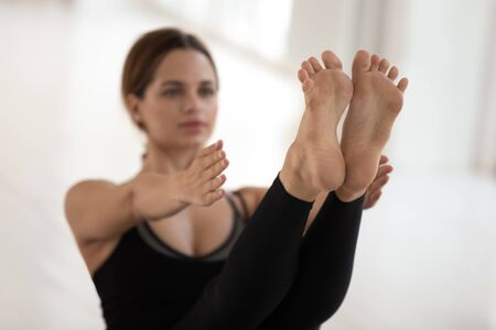 Beautiful young woman doing Paripurna Navasana exercise, boat pose, practicing yoga, feet close up, attractive sporty girl wearing black sportswear working out at home or in yoga studio
