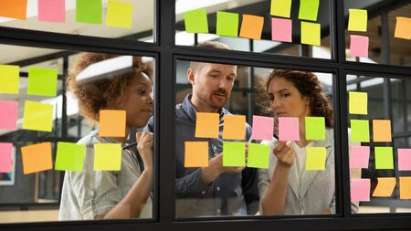 Foto de Diverse business team people share ideas brainstorm on corporate project strategy write ideas on post it sticky notes organize work process together look at glass scrum board at teamwork briefing - Imagen libre de derechos