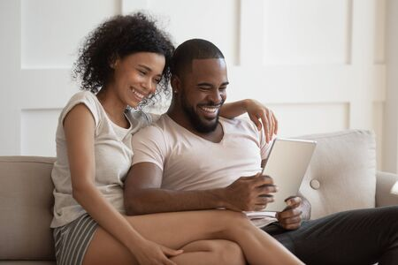 Photo pour Smiling african american young woman cuddling happy husband, sitting on cozy sofa in living room at home, using tablet together, shopping or watching funny movies, photos, spending free weekend time. - image libre de droit