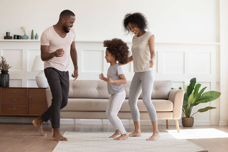 Foto de Happy african american family having fun, dancing at home. Smiling carefree cheerful black daddy, mommy and little kid daughter playing enjoying spending time together in modern living room. - Imagen libre de derechos
