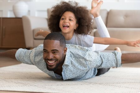 Foto de Happy african american dad lying on floor carpet with cute daughter on back, pretending to be planes. Overjoyed smiling girl enjoying weekend time with daddy, playing, laughing. Active family leisure. - Imagen libre de derechos