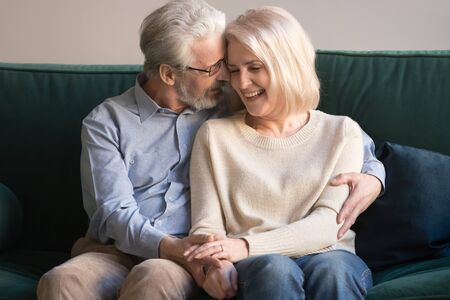 Foto de Middle aged gray-haired relaxed caring man hugging senior smiling happy blonde wife, supporting, holding hands, expressing love, tenderness, leaning head to head, sitting on sofa, resting at home. - Imagen libre de derechos