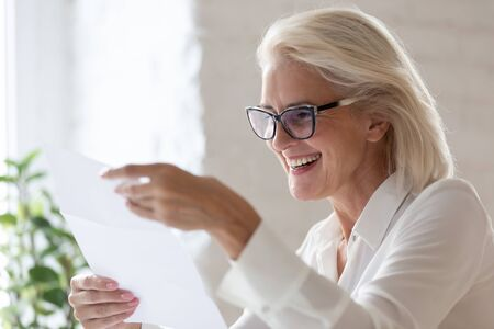 Smiling aged businesswoman hold paper document read good news in correspondence, happy senior woman worker look through paperwork feel excited overjoyed with approval letter or contract