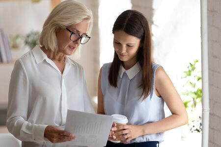Foto für Diverse female employees stand discussing company financial statistics, woman banking specialists hold paper report cooperating talk consider paperwork stats, senior employer show graph to colleague - Lizenzfreies Bild