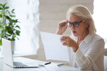 Foto de Surprised aged woman worker in glasses sit at office desk reading paper document or contract feel confused with bad news, frustrated senior businesswoman stunned by received paperwork correspondence - Imagen libre de derechos