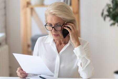 Photo pour Concentrated senior businesswoman in glasses sit at office desk talk on cellphone reading paperwork document, focused middle-aged woman speak with client on smartphone discuss contract - image libre de droit