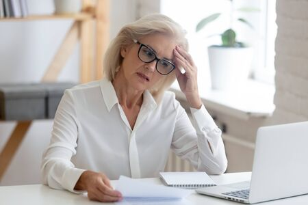 Photo pour Pensive aged businesswoman in glasses sit at office desk thinking of problem solution, thoughtful senior woman worker in glasses look at laptop screen hold document pondering or making decision - image libre de droit