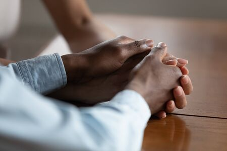 Photo pour Close up of african American couple hold hands on wooden table make peace reconcile after fight, biracial husband and wife show love, care and support, have romantic intimate moment. Devotion concept - image libre de droit