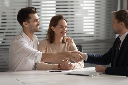Photo pour Happy family young couple shaking hands with financial advisor, lawyer, realtor, broker, bank worker, thanking for consultation, accepting loan or medical insurance offer, buying services at office. - image libre de droit