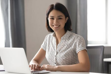 Foto de Happy motivated asian female employee hr manager team leader working with computer at modern office portrait. Smiling confident mixed race business woman, professional coach trainer looking at camera. - Imagen libre de derechos
