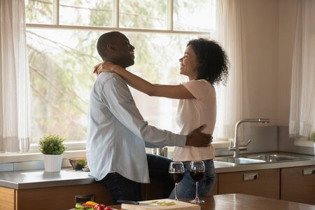 Photo pour Loving happy african American husband and wife hug enjoy romantic dinner date on kitchen, smiling biracial couple drink wine embrace celebrating wedding anniversary at home, celebration concept - image libre de droit