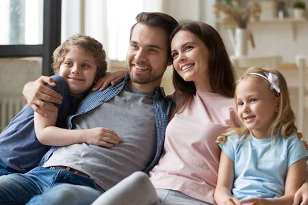 Photo pour Happy parents sitting with smiling children siblings at comfortable couch in living room, enjoying spending free weekend time together. Joyful family of four cuddling, bonding, entertaining at home. - image libre de droit