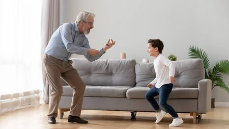 Photo pour Cute little boy grandson having fun dancing with old elderly grandpa in living room, happy two generation active family senior grandfather and small grandchild playing enjoying time together at home - image libre de droit