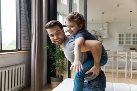 Photo pour Portrait of happy daddy giving piggyback ride to adorable cute little kid son. Joyful family of two playing together in modern living room at home. Laughing boy enjoying home activity with young dad. - image libre de droit