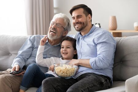 Foto de Happy multi three 3 generation men family hold snack remote control watch tv show sit on sofa together, little boy son grandson young father and old grandfather laugh view television at home on couch - Imagen libre de derechos