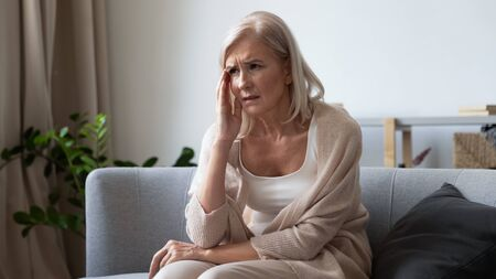 Foto de Unhappy mature woman touching head, feeling strong headache, sitting on couch at home alone, upset older female suffering from migraine or high blood pressure, health problem concept - Imagen libre de derechos