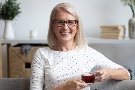 Photo pour Head shot portrait smiling mature woman holding cup of black tea with tea bag inside, mature female sitting on couch, relaxing at home, drinking enjoying hot beverage in mug in the morning - image libre de droit