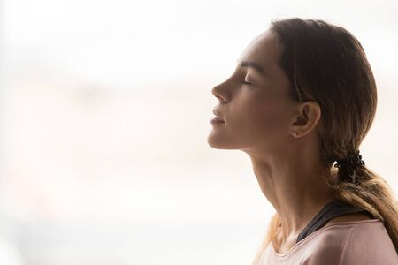 Photo pour Serene young woman taking deep breath of fresh air relaxing meditating with eyes closed enjoying peace, calm girl tranquil face doing yoga pranayama exercise feel no stress free relief, side view - image libre de droit