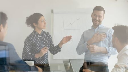 Happy male worker coach laugh thank for appreciation at corporate training presentation, indian teacher manager rewarding praising grateful pleased employee in boardroom behind glass, recognition