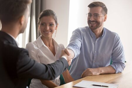 Foto de Happy young couple or hr team handshake lawyer broker job applicant make business deal at meeting interview, family clients shake hand of insurer thanking for consulting buying insurance services - Imagen libre de derechos