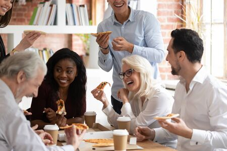 Photo for Overjoyed multiracial employee have fun eating pizza drinking coffee in office together, smiling happy diverse colleagues having lunch break laughing enjoying Italian fast food takeaway delivery - Royalty Free Image