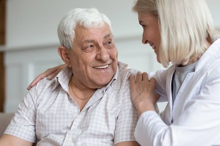 Photo pour Middle-aged nurse hug elderly man patient sitting on couch look at each other having warm relations understating. Concept of caregiving solve problems together helping give mental or physical support - image libre de droit