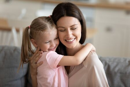 Photo for Happy loving mother embracing little daughter close up, enjoying free time together at home, smiling mum and adorable preschool child hugging and cuddling with closed eyes, trusted good relationship - Royalty Free Image