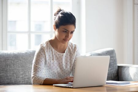 Photo pour Focused Indian woman using laptop at home, looking at screen, chatting, reading or writing email, sitting on couch, serious female student doing homework, working on research project online - image libre de droit