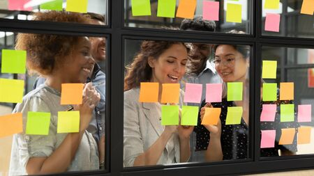 Photo pour Positive multi-ethnic group of business people working together on new project writing main topics sharing creative ideas thoughts using colourful sticky notes, concept of synergy and teamwork - image libre de droit