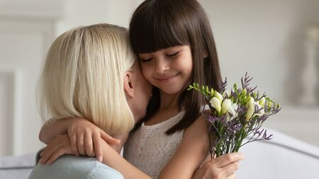 Photo for Close up head shot little cute schoolgirl embracing middle aged grandmother, congratulating with birthday, international woman day. Small adorable granddaughter prepared flowers as present to granny. - Royalty Free Image
