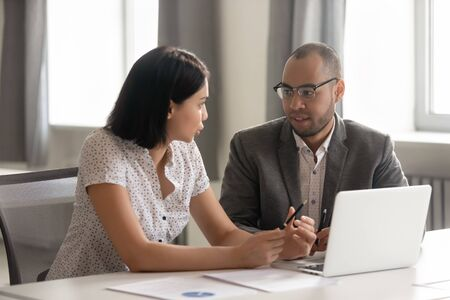 Photo pour African American businessman and Asian businesswoman discussing project statistics, analyzing results, discussing strategy, working together, mentor helping new employee with software, using laptop - image libre de droit