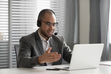Foto de Smiling African American employee in headset using laptop, talking, call center operator agent in headphones with microphone consulting client customer, student learning language online - Imagen libre de derechos