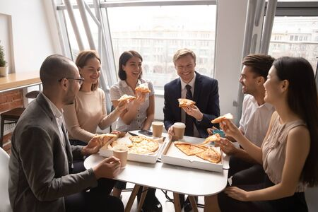 Photo pour Happy diverse employees having fun, enjoying pizza together, colleagues sharing meal at lunch break, office workers team eating Italian fast food, laughing at funny joke, good relations - image libre de droit