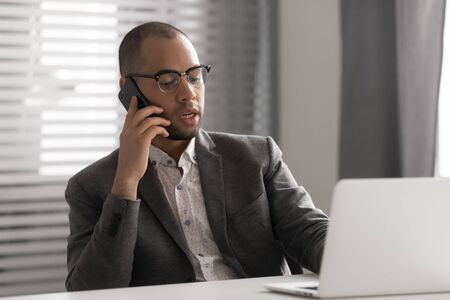 Photo pour Serious African American businessman in glasses talking on phone, using laptop, having business conversation, hr manager holding interview by cellphone, employee consulting client, making sell offer - image libre de droit