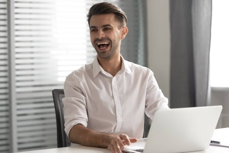 Happy businessman laughing at joke, shouting, sitting at office desk with laptop, employee intern receive funny news, having fun, feeling joy at work, positive emotions, excited by success