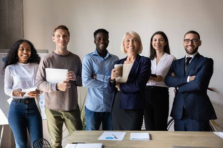 Foto de Happy confident diverse old and young business people stand together in office, smiling multiethnic professional colleagues staff group look at camera, human resource concept, team corporate portrait - Imagen libre de derechos
