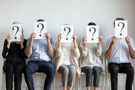 Foto de Unemployed professional business people candidates group sit on chairs in row line queue holding sheets with question mark hiding face waiting for job interview, human resources and recruit concept - Imagen libre de derechos
