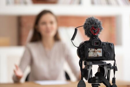 Foto de Focus on foreground camera screen show live recording video blog, confident millennial woman seated in front of cam filming educational video for online university course, share professional knowledge - Imagen libre de derechos