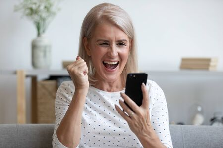 Foto de Overjoyed mature old woman hold phone looking at screen feel excited about mobile online app bid win, happy middle aged lady winner celebrate victory success read message good news in cell at home - Imagen libre de derechos