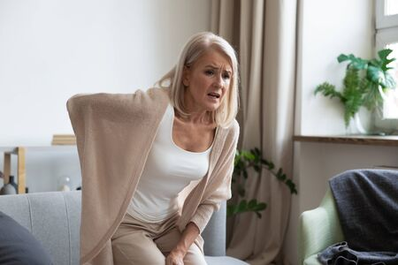 Foto de Worried upset middle aged mature woman feel hurt sudden back ache touch sore spine at home alone, tired mature senior grandmother having lower lumbago backache injury spinal pain, backpain concept - Imagen libre de derechos