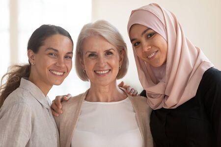 Foto de Three happy beautiful diverse two generation women young asian muslim woman wear hijab and caucasian older mature female multicultural ladies bonding standing together looking at camera, portrait - Imagen libre de derechos