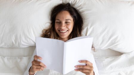 Top above view head shot close up happy mixed race young woman waked up in morning, lying on comfortable white pillows under warm blanket, enjoying reading funny stories in favorite book at home.
