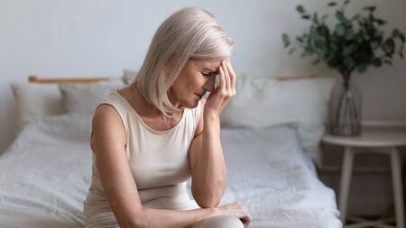Sick older mature woman sit on bed feel pain dizziness coping with morning headache concept, upset tired middle aged adult woman touching sore head suffer from terrible migraine mental problem