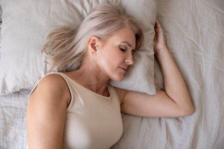 Photo pour Peaceful healthy beautiful 50s mature woman lying asleep on comfortable pillow orthopedic mattress sleeping well in cozy bed alone, calm serene old female resting in bedroom, close up top view - image libre de droit